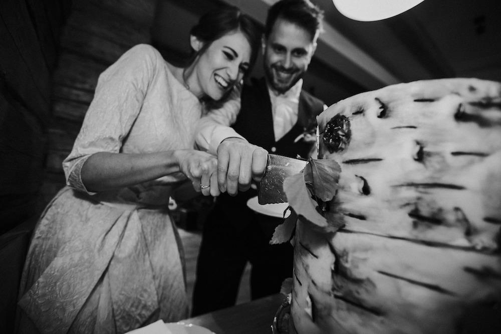 Novomanželé krájí společně svatební dort.