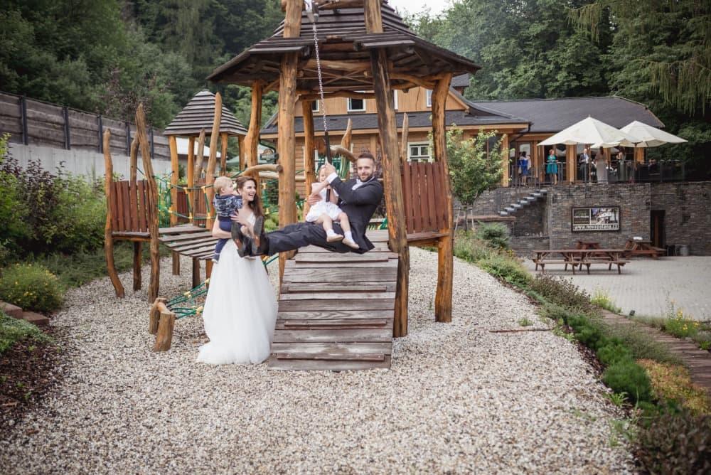 Společné foto novomanželů na dětském hřišťi