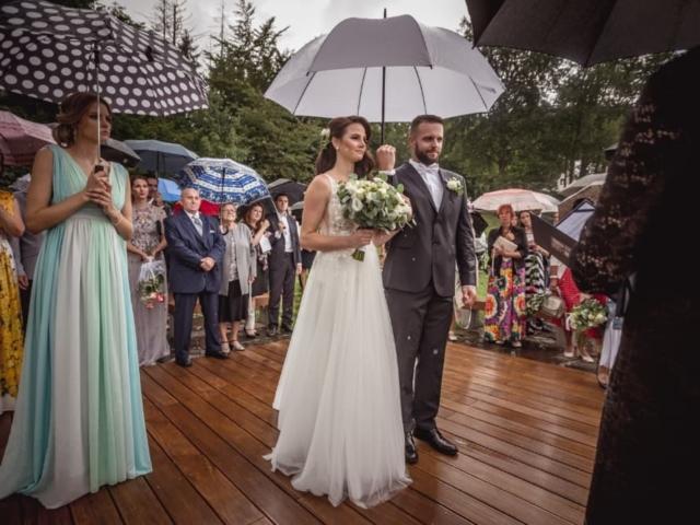 Svatební obřad na louce v děšti - ženich drží deštník
