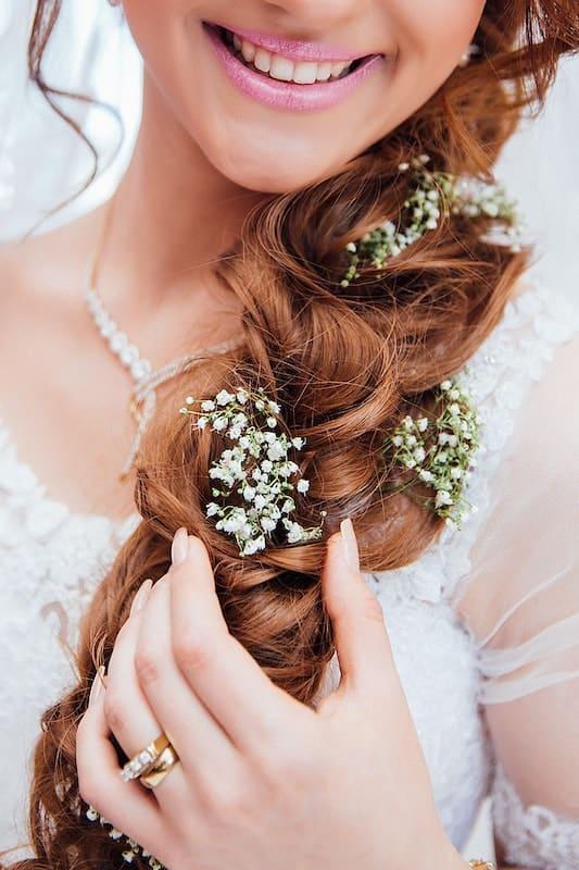 Svatební účes s vpletenými kvítky.